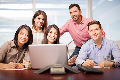 A group of males and females behind a desktop computer smiling.