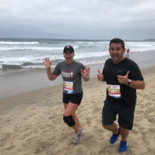 Employees in a race running on the beach