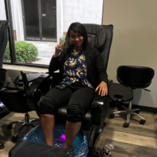 Another woman in a comfy chair with her feet in a foot bath flashing the peace sign.