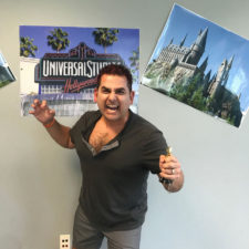 A man in front of poster of Universal Studios