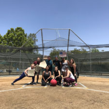 Employees on a softball field with a big red ball