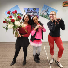 Three women employees dressed up for party. One is holding flowers.